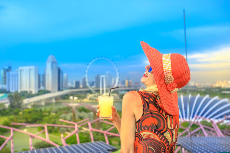 Travel holiday vacation in Singapore, Southeast Asia. Lifestyle caucasian woman with wide hat drinking aperitif at rooftop. Aerial view or cityscape skyline. Happy tourist enjoying at marina bay. Singapore Singapore City Woman Tourist Tourist Attraction  Tourist Destination People Girl Females Aerial View Skyline Cityscape Panorama Happy Travel Hat Lifestyle Enjoy Nature Tourism Smiling Aperitif Drink Orange Juice  Analcolic Glass One Person Focus On Foreground Sky Refreshment Food And Drink Holding Adult Lifestyles Architecture Leisure Activity Women Alcohol Drinking Day Building Exterior Cloud - Sky Outdoors Cocktail Hand