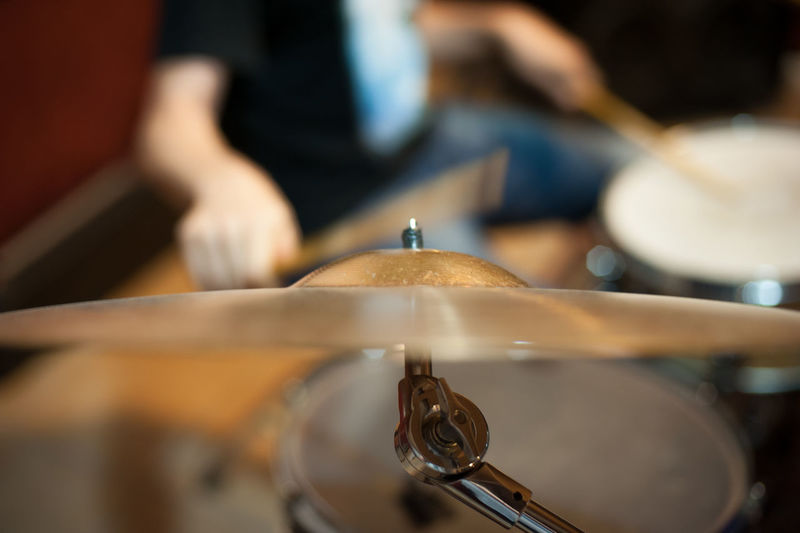 Close-Up Of Cymbal With Musician In Background