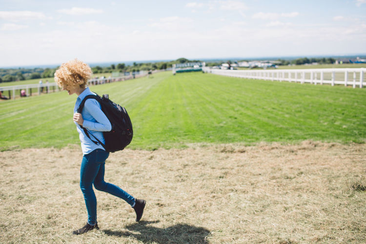 Side view of young woman walking at epsom downs racecourse during sunny day