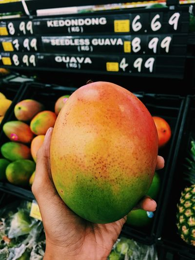 Cropped hand holding mango in supermarket
