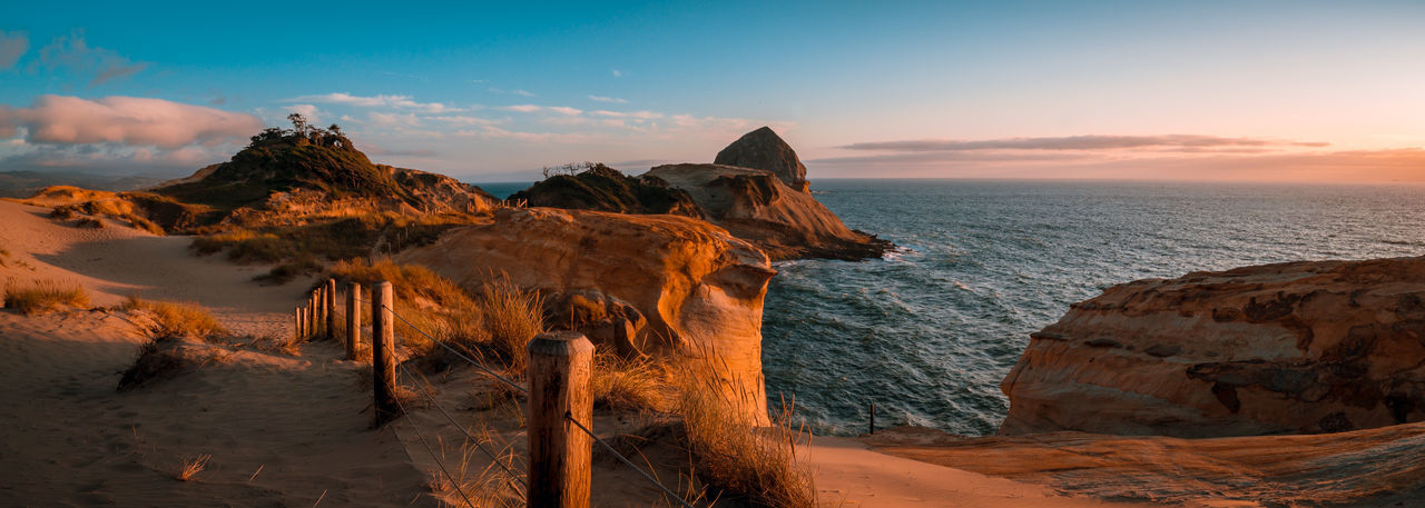 Rock formations on shore against sky during sunset