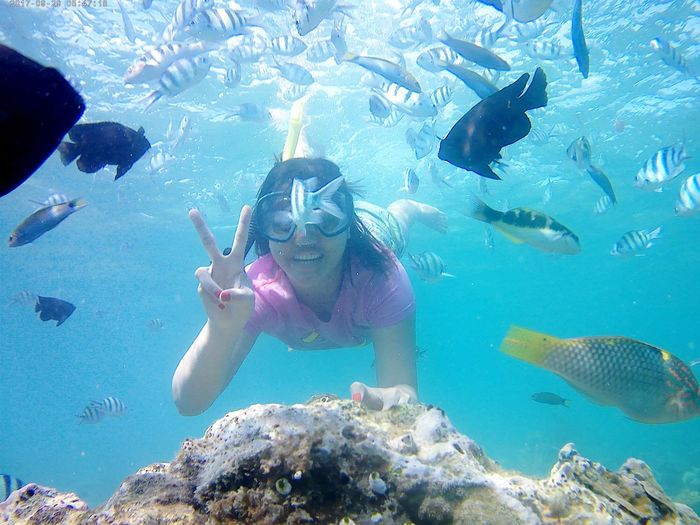 Carefree woman showing peace sign while swimming in sea