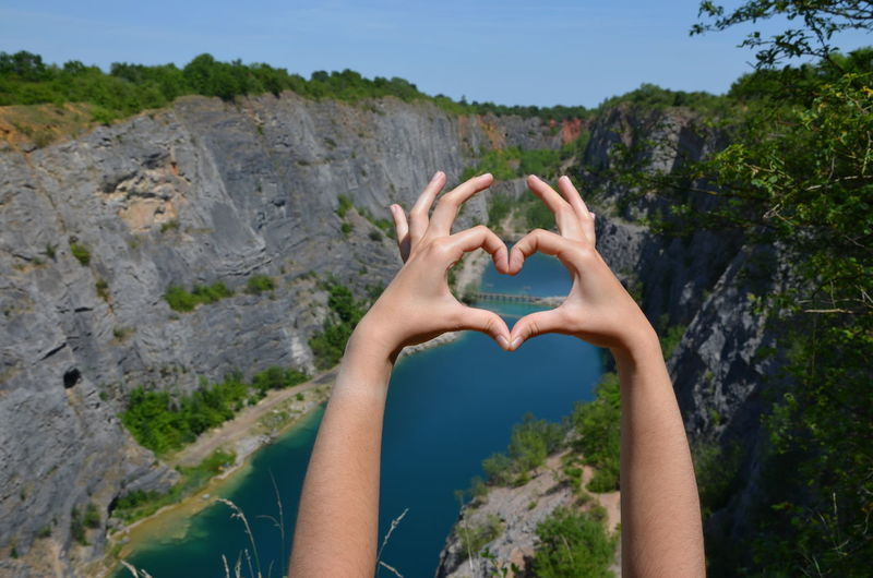 Cropped hands of woman making heart shape against mountains and sky