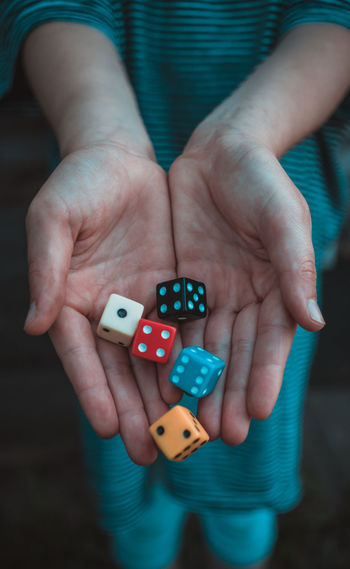 Midsection of girl holding dices