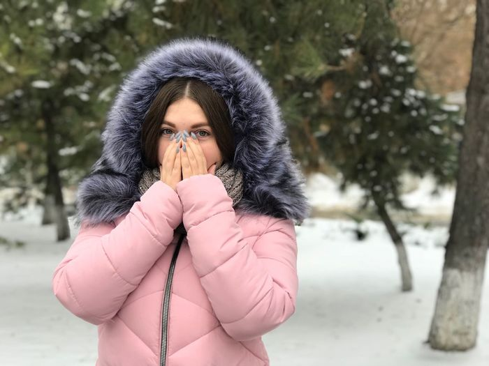 Portrait of young woman wearing warm clothing while standing against trees during winter