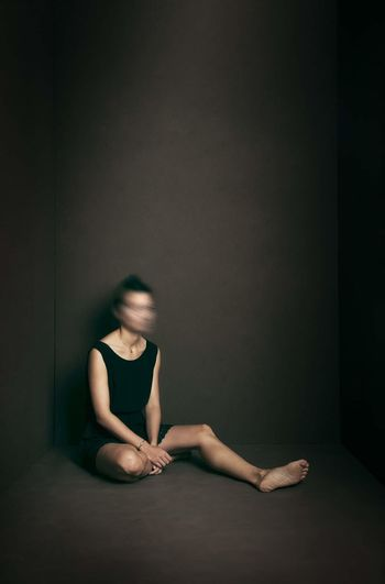 Midsection of woman sitting against black background