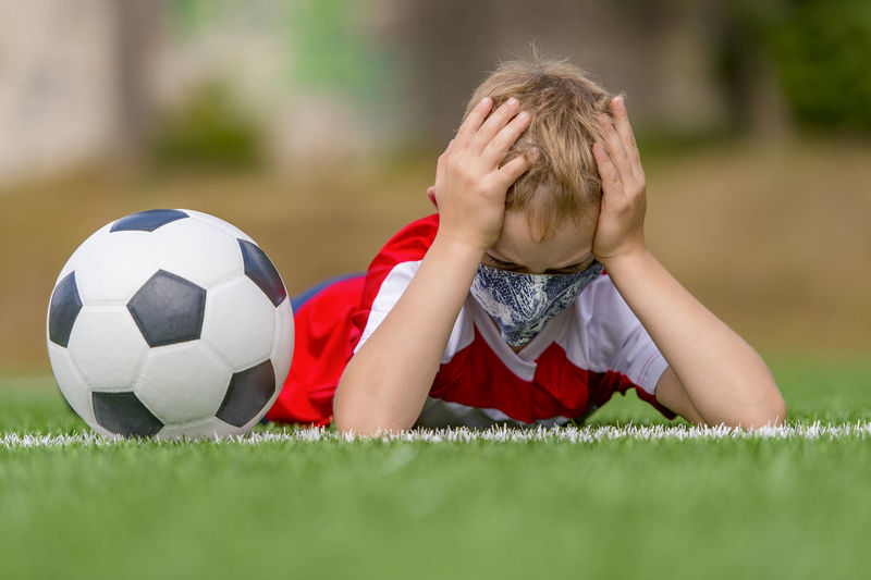 Boy wearing mask lying down with soccer ball on field