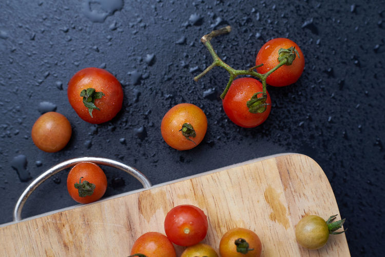 High angle view of wet tomatoes with cutting board on slate