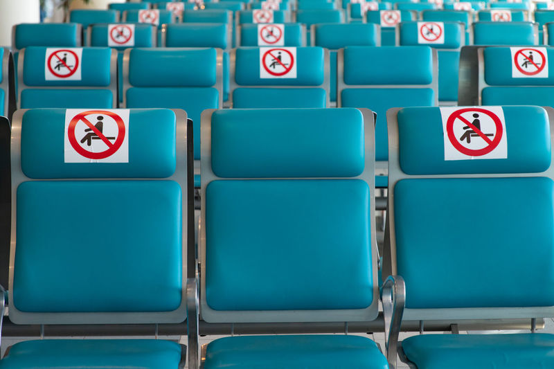 Airport during coronavirus pandemic. social distancing. empty blue chairs restricted no-sitting sign