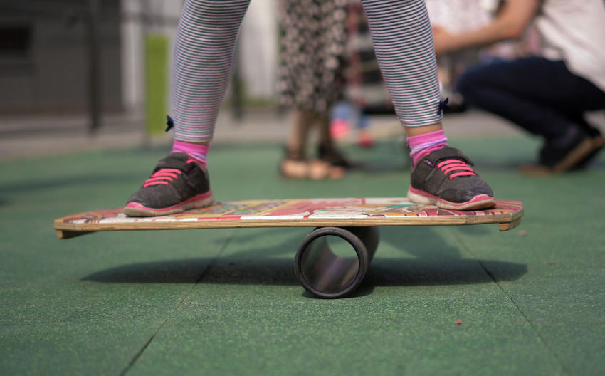 Low Section Of Woman Skateboarding In Park