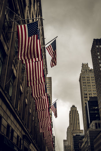 Low angle view of flags against buildings in city