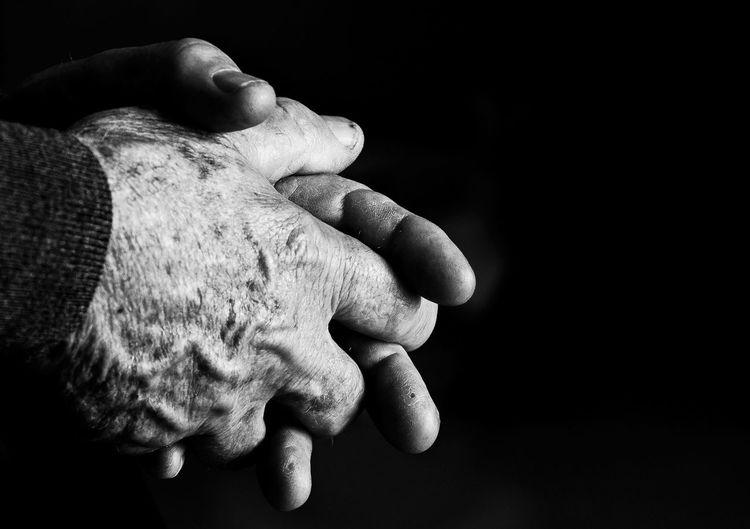 Cropped image of person with hands clasped against black background
