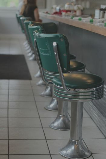 Green Chairs Arranged By Table In Cafe