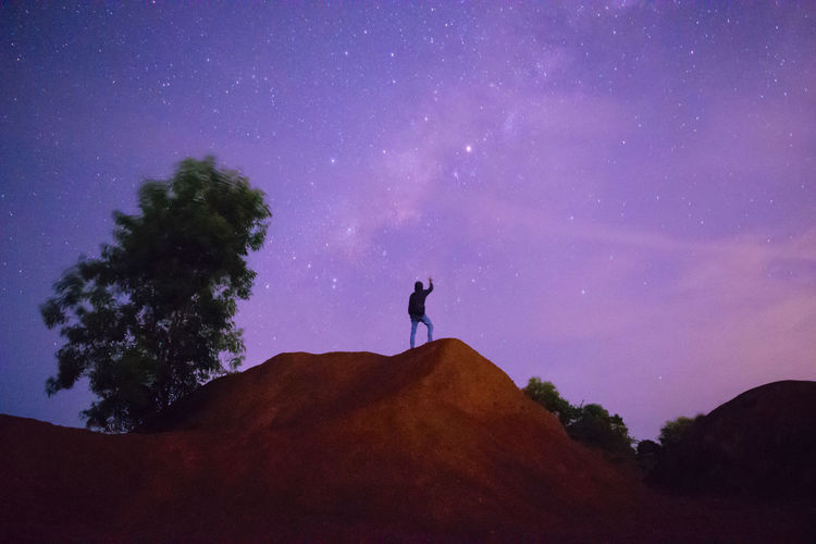 Silhouette man standing on rock against sky at night