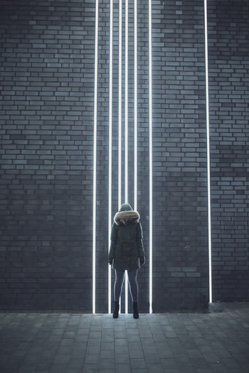 Full length of woman standing against illuminated lights on wall