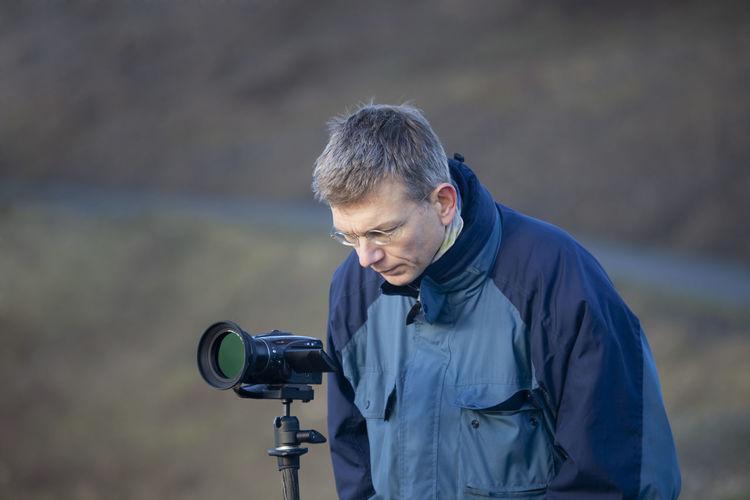 Mature man looking at digital video camera