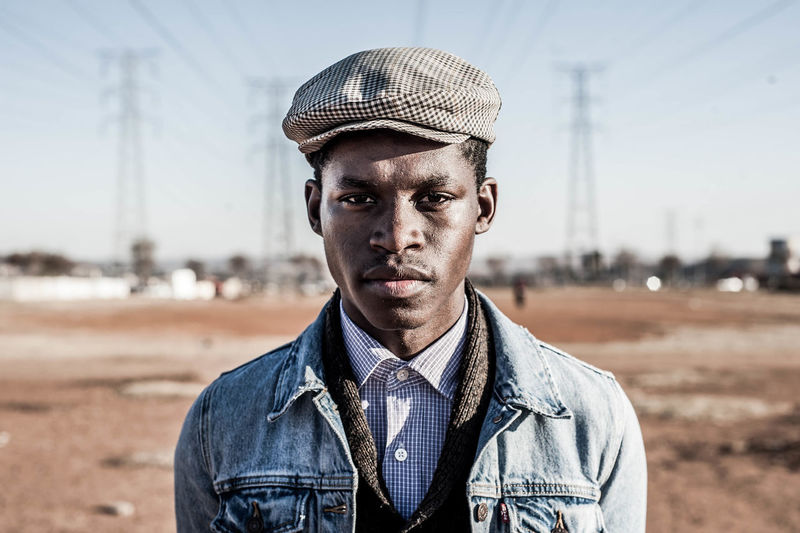Portrait of young african man wearing cap while standing against sky