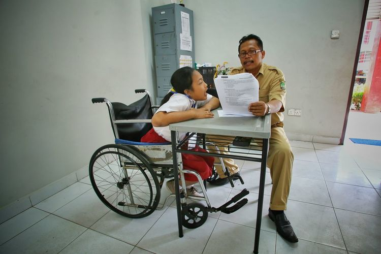 Police Officer Reading Document By Disabled Girl On Wheelchair In School Office