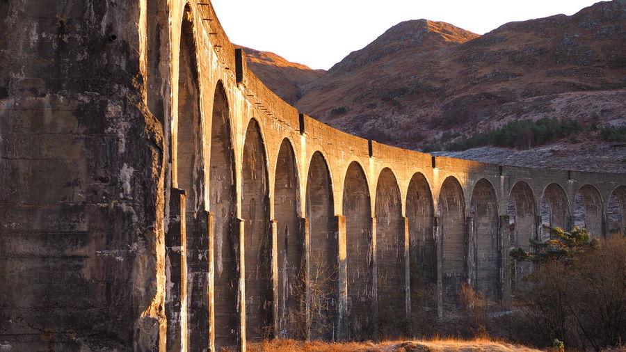 Arch bridge over mountains against sky