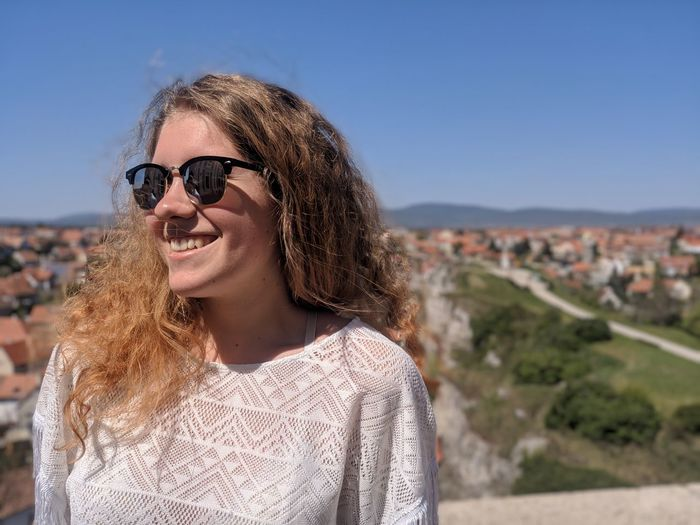 Young woman wearing sunglasses standing against clear blue sky