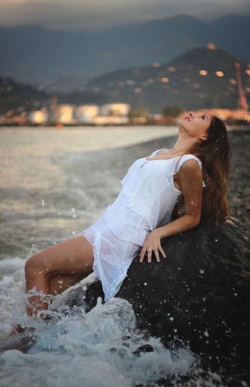 Beautiful woman lying on rock in sea at dusk