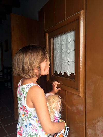 Girl looking at a wasp in window One Person Real People Child Girls Females Leisure Activity Casual Clothing Standing Window Floral Pattern Side View Innocence Door Lifestyles Childhood Waist Up Street Doors Old Door Holding Notice Curiosity Summer Clothing Doll