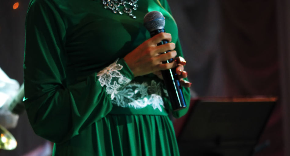 Midsection of woman in traditional clothing holding microphone while standing on stage