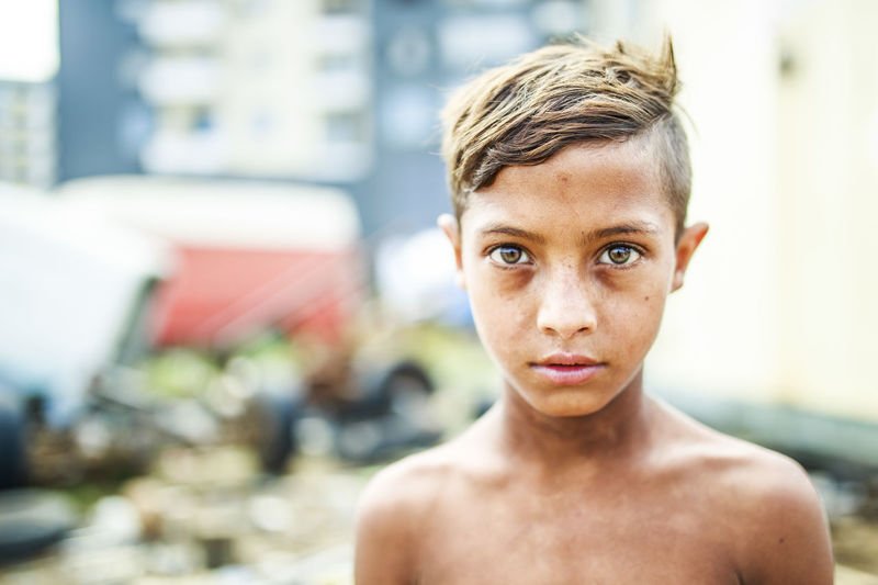 Portrait of shirtless boy standing outdoors