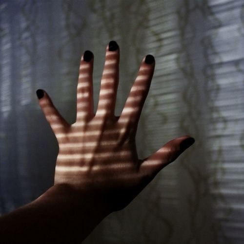 Cropped hand of woman against wall
