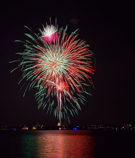 Low angle view of illuminated fireworks over lake against sky at night