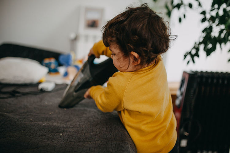 Rear view of child with vacuum cleaner at home