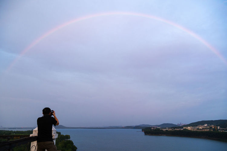 Rear View Of Man Photographing Rainbow Over Sea Against Sky