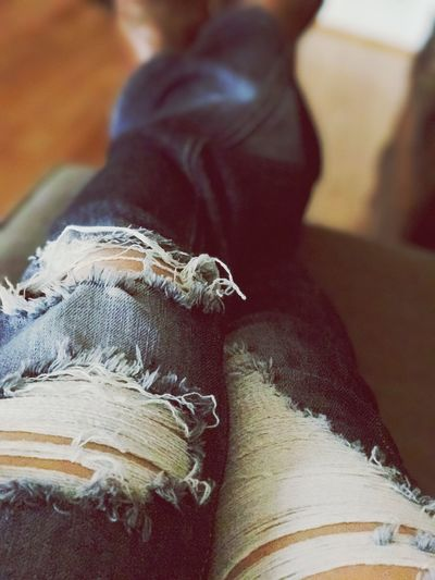 Relaxing with Legs Kicked Up Lifestyles Freshness Close-up One Person Real People Human Body Part Indoors  Torn Jeans Ripped Jeans Leg Shot Jeans Shot Legs Up Kicked Back Relaxed Resting Legs Relaxing Time Taking A Break Jeans Tattered Jeans Holes In Jeans Holey Jeans Resting On Couch