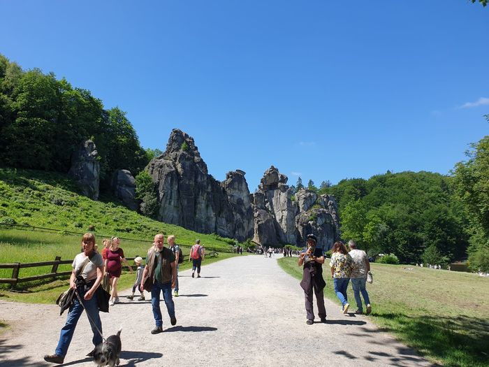People walking on mountain against blue sky
