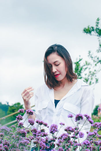 Beautiful young woman holding purple flowering plants against sky