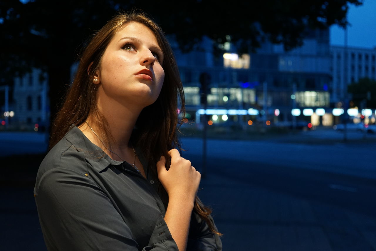 Thoughtful Beautiful Woman Looking Up In City