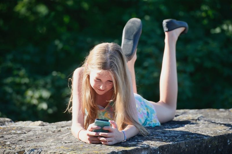 Girl using smart phone while lying on retaining wall outdoors