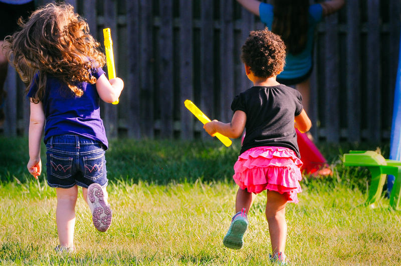 Two Young Girls Playing with Bubbles Child Childhood Children Only Curly Hair Elementary Age Females Friendship Front Or Back Yard Full Length Fun Girls Outdoors People Playing Rear View Summer Togetherness Two People