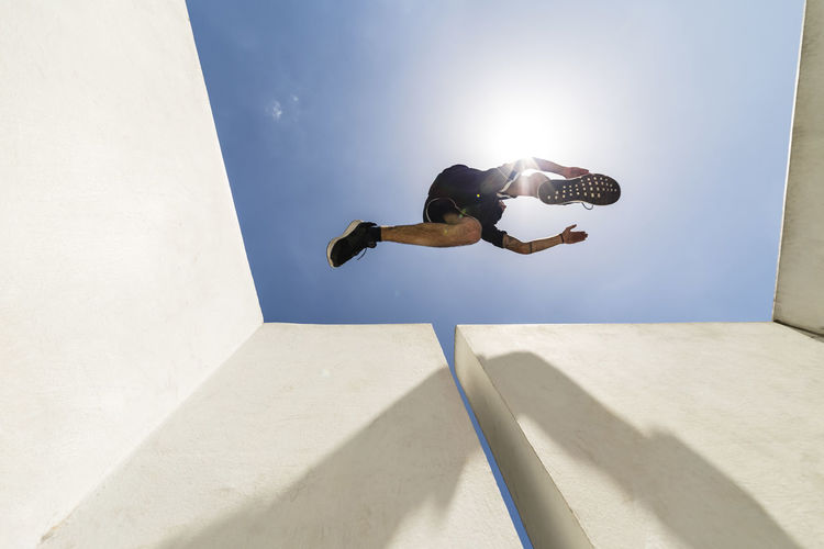 Low angle view of man jumping on concrete against sky