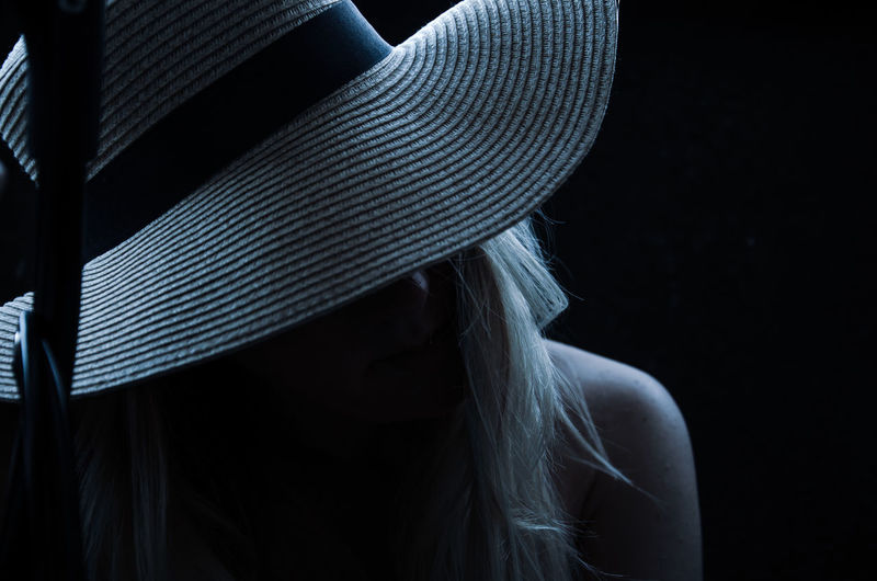 Close-up portrait of woman wearing hat against black background
