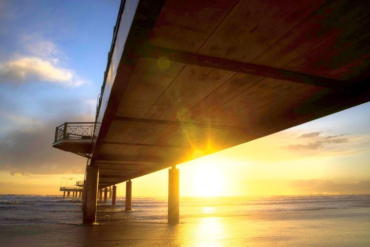 Sky Sea Water Cloud - Sky Sunset Horizon Over Water Horizon Architecture Built Structure Scenics - Nature Sun Nature Beauty In Nature Beach No People Orange Color Sunlight Land Outdoors Lens Flare Architectural Column