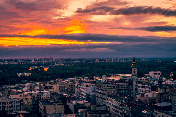 High angle view of city against cloudy sky during sunset