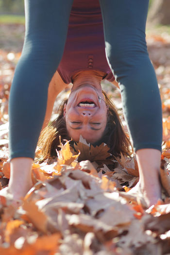 Low section of woman with autumn leaves