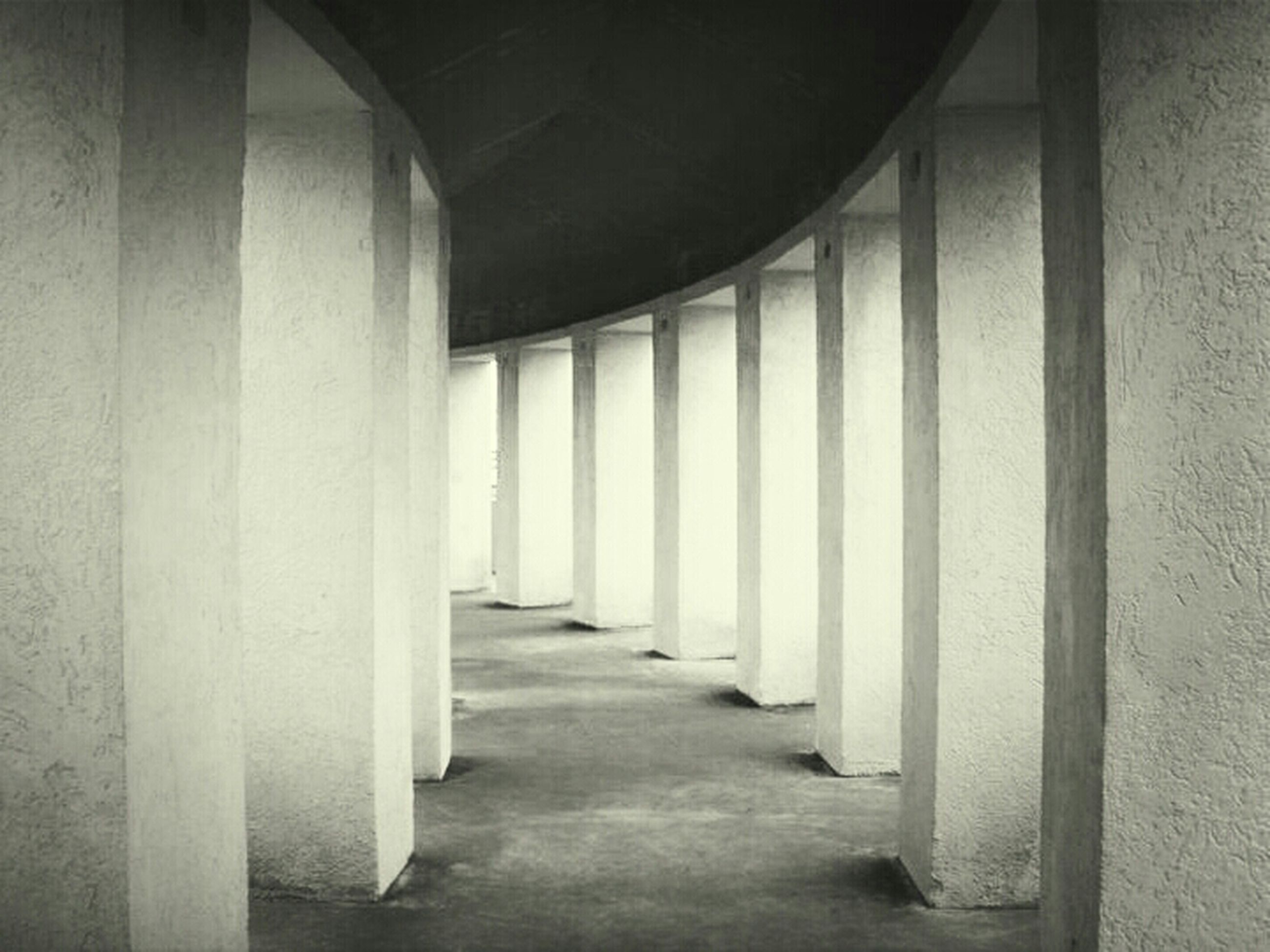 architecture, built structure, indoors, corridor, the way forward, door, architectural column, window, building, column, wall - building feature, empty, building exterior, sunlight, diminishing perspective, wall, doorway, entrance, day, no people