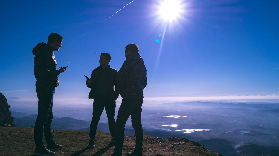 Male friends standing on mountain against blue sky