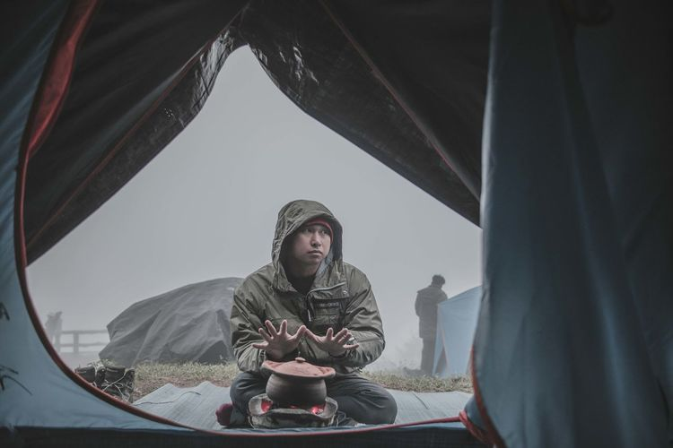 Man Wearing Warm Clothing While Sitting By Camping Stove Seen Through Tent