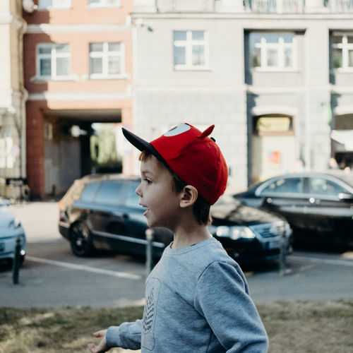 Architecture Boys Building Exterior Built Structure Cap Car Casual Clothing City Day Focus On Foreground Hat Land Vehicle Leisure Activity Lifestyles Males  Mode Of Transportation Motor Vehicle One Person Outdoors Real People Transportation