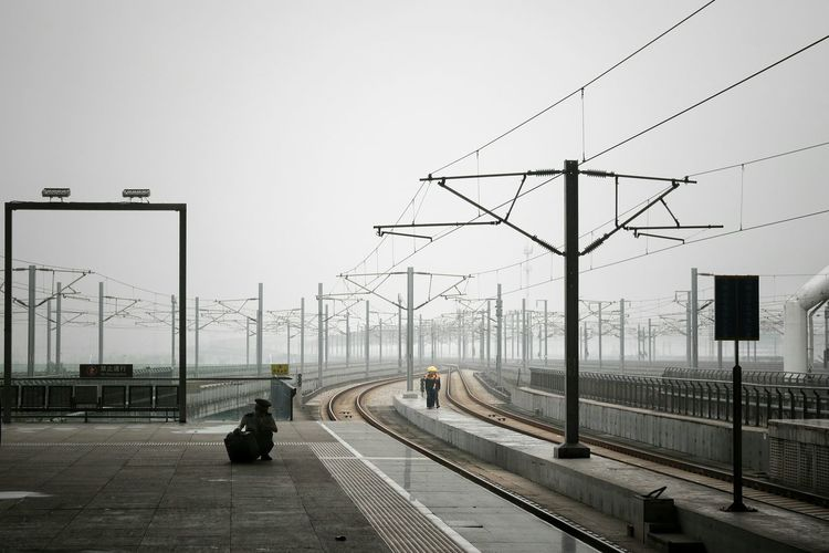 Power Lines Over Railroad Tracks Against Cloudy Sky