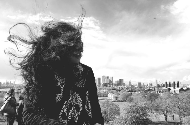 Woman With Tousled Hair Against Sky On Windy Day In City
