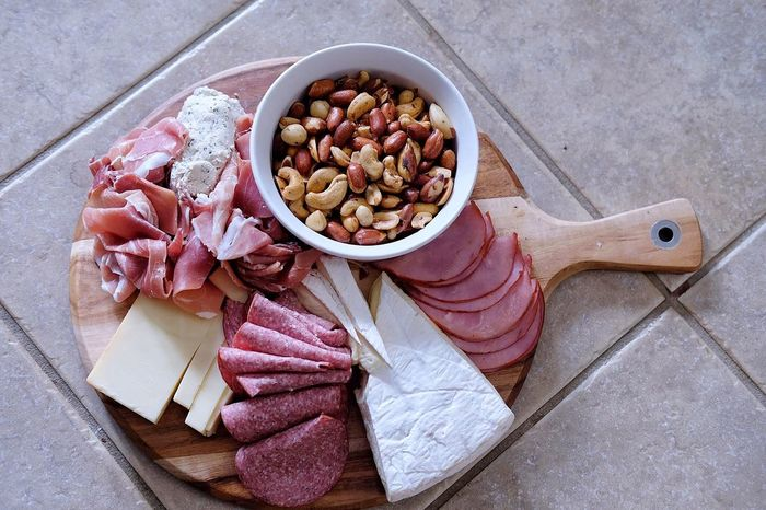 High angle view of deli meats and cheeses abd assorted nuts on cutting board Nuts Assorted Nuts Board Bowl Cheeses Cheesesteak Close-up Cutting Board Delicious Food Food And Drink Foodphotography Freshness Healthy Eating High Angle View Indoors  Kitchen Utensil Meat No People Party Processed Meat Still Life Table Vegetable Wellbeing